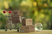Shopping Online and e-commerce concept: Paper boxes in shopping cart and crystal globe. Trading management system so that customers can buy products and services from that operator at all times