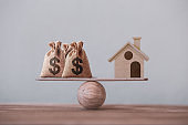 US dollar hessian bags with house paper model on a wood balance scale. Home loan, reverse mortgage concept, Depicts a homeowner or a borrower turns properties into cash