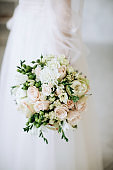 Wedding flowers. The bride holds a beautiful wedding bouquet of roses