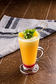 Winter hot drink from oranges and berries in tall glass on wooden table