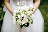 bride holding a beautifuk wedding bouquet with white roses