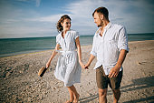 Loving happy young couple walking on the beach. Summer vacation