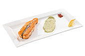 Grilled salmon fillet with lemon and guacamole sauce on white plate isolated on white background