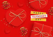 Happy Valentine's Day. Romantic background design with realistic red gifts box in the shape of heart. Flowers roses, gold and red buds. Bright shiny confetti. Holiday poster, banner, greeting card