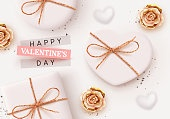 Happy Valentine's Day. Romantic background design with realistic white gifts box in the shape of heart. Flowers roses, gold and beige buds. Bright shiny confetti. Holiday poster, banner, greeting card