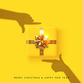Merry Christmas and Happy New Year. Yellow background with realistic festive gifts box. Effect of the shadow of hands is holding a gift in focus. Photo Frame Hands Made by Young Girls. Xmas present