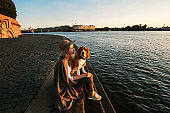 Calm woman with dog on hands sitting on embankment and looking at river