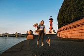 Smiling woman jogging with dog along embankment of river
