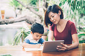 Son using digital tablet computer for study and learn to internet online with mother together, education from home, family recreation, mom teach boy and homework with technology, lifestyle concept.