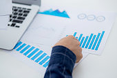 Hand of young business man pointing document data graph and chart paper, marketing and investment, report of statistics profit for financial, economic and growth of finance, management and planning.