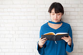 Beautiful of portrait young asian woman happiness relax standing reading book on concrete cement white background, girl happy study content literature, education and lifestyle concept.