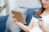 Young asian woman smiling holding credit card shopping online with tablet computer buying and payment, girl using debit card purchase or transaction of finance, lifestyle and e-commerce concept.