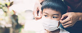 Mother take care son with face mask for protection disease flu or covid-19 outdoors, mom wearing on medical mask with child safety for protect outbreak of pandemic, medical concept, banner website.
