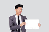 Young asian business man showing empty signboard for advertising isolated on white background, businessman confident holding billboard banner for presenting with copy space, success and achievement.