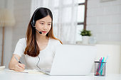 Young asian woman wearing headphone study online with e-learning on desk, girl wearing headset learning to internet with laptop computer at home, new normal, distance education and training.
