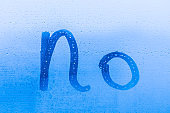 The creative inscription no on the blue evening or morning window glass with drops