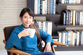 Beautiful young asian woman sitting on chair with comfort and relaxing in living room at home drinking a cup of coffee or tea or beverage, lifestyle asia girl leisure healthy and wellness for satisfied.