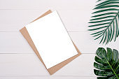 Blank paper sheet copy space with mockup and leaf on wooden table, poster and notebook, postcard decoration your design or branding, simplicity and minimal, nobody, flat lay, top view.