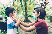 Mother take care son with face mask for protection disease flu or covid-19 outdoors, mom wearing on medical mask with child safety for protect outbreak of pandemic in public, medical concept.