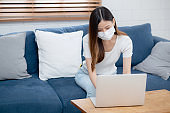 Young asian business woman in face mask work from home on laptop computer online to internet in living room, girl in medical mask and quarantine for pandemic of covid-19, stay home, new normal.