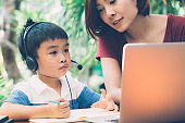 Young asian mother and son using laptop computer for study and learning together at home, boy writing on notebook for homework and wearing headphone, teacher or mom support child, education concept.