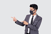 Portrait young asian businessman in suit wearing face mask for protective covid-19 isolated on white background, business man presenting and showing, quarantine for pandemic coronavirus, new normal.