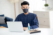 Young business man in face mask working from home with laptop computer on desk for protection for outbreak of covid-19 and healthcare, male quarantine stay home using notebook on desk, new normal.