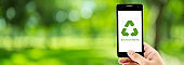 Smart phone holding hand with recycle symbol eco environment Icon concept with green bokeh background, ecology conservation and reuse, reduce using and protection resources in nature, banner website.