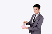 Young asian businessman in suit deposit money dollar with piggy bank isolated on white background, business man saving with planning budget and finance for success investment and financial.