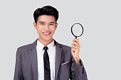 Young asian business man in suit look magnifying glass for search isolated on white background, businessman expression and find quality, inspector and scrutiny, male expression.