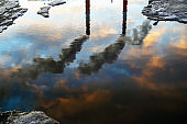 Reflection in puddle of three smoked industry chimneys. Air pollution concept.