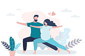 Happy love couple standing in yoga pose. Beauty pregnant woman and handsome man doing asana.
