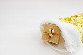 Gift box wrapped in kraft paper and tied sack rope in yellow christmas sock on white background