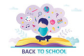 Schoolboy sitting on open book. Concept of back to school, education. Boy thinks about stationery, supplies and learning