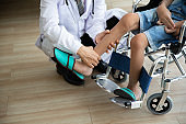 Doctor checking disabled person pateint leg at hospital, Muscle weakness