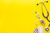 Pills, stethoscope - cold, flu and virus treatment. on yellow desk from above space for text