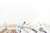Treatment of influenza or cold. Medicine, stethoscope on white table top-down copy space
