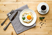 Fried egg on plate on wooden table top view copy space