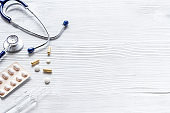 Treatment of influenza or cold. Medicine, stethoscope on white wooden table copy space