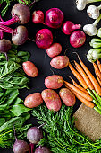 Carrot, potato, beet, onion and spinach on black background top view