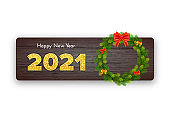 Golden numbers 2021. Holiday gift card Happy New Year with Christmas wreath and bows on wood background. Celebration decor. Vector template illustration