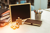 Thick wood jigsaw on the table near book, pencil case and blackboard. Education learning and grow up  concept.