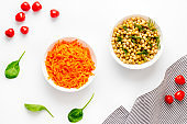 Vegetarian meal. Chickpeas and carrot in bowls on white table top view