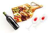 Red wine and snacks set on cutting board top view