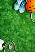 Sport balls and badminton rackets on football grass. Top view copy space