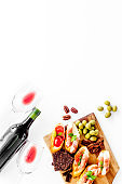 Wine appetizer. Toasts, nuts, olives on white desk top view copy space
