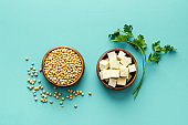 Tofu cubes in bowl and soybeans on blue kitchen table top-down