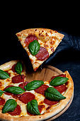Hand holds a slice of delicious pizza isolated path on a dark background with sausage and spinach