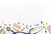Pills, stethoscope - cold, flu and virus treatment. on white desk from above space for text