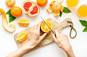 Hands cutting citrus fruit on board top view